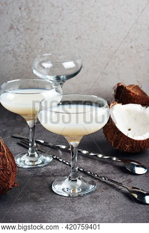 Pina Colada Liqueur In A Glass And Coconut Halves.