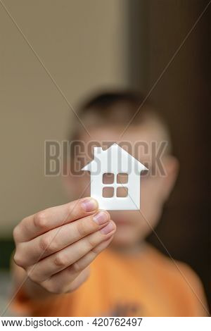 Orphanage, Children In The Orphanage. The Child Is Holding A Small House-shaped Figurine, Close-up.