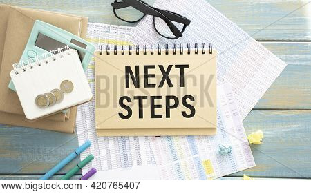 Next Steps Written On A Card Lying On The Table Next To A Notebook