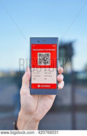 Hand Man Holds Smartphone Displaying An App Mobile Expired Digital Green Vaccination Certificate For