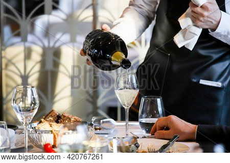 The Waiter Pours White Wine Into The Glass. Banquet, Cutlery, Table Setting.