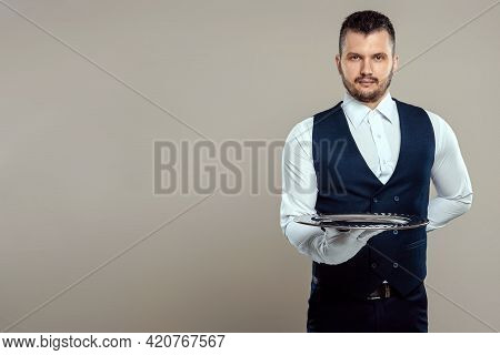 Handsome Male Waiter, White Shirt, Holds A Silver Tray, Hand Behind His Back. Concept Of Wait Staff