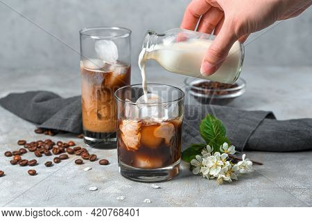 A Woman's Hand Pours Milk Into A Glass Of Coffee With Milk On A Gray Background. Preparation Of A Re