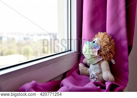 A Teddy Bear Waering A Medical Protective Mask Sits On A Windowsill And Looks Out The Window. Sadnes
