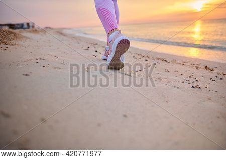 Closeup Of Runner Legs In Pink Sports Shoes Performing Jog On A Sandy Beach During Sunrise In The Ea
