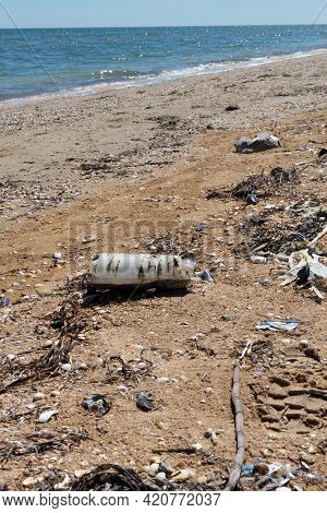 An Old, Semi-decomposed Plastic Bottle, Plastic Bags And Other Garbage Lie On The Seashore.