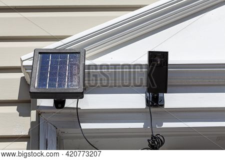 A Wireless Security Surveillence Camera With Motion Sensor On Top Of The Front Door Frame. The Camer