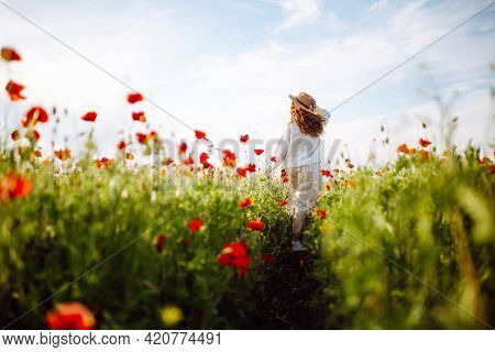 Girl In A Hat With Long Curly Hair Posing In A Field With Red Flowers. Summer Landscape. Warm Colors