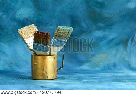 Paint Brushes In A Gilded Metal Mug On A Blue And Gilded Background. Selective Focus. Copy Space.