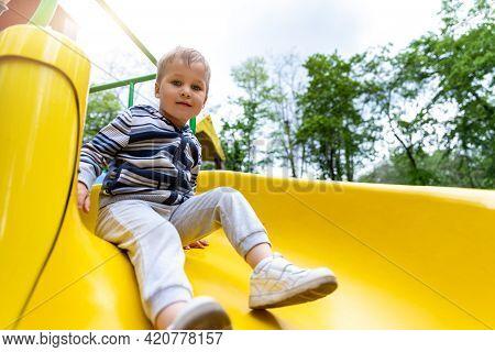 Portrait Of Cute Little Cute Caucasain Blond Toddler Boy Enjoy Having Fun Sliding Down Modern Plasti