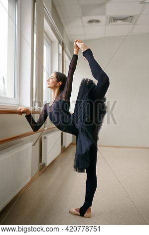 Ballerina doing stretching exercise at barre