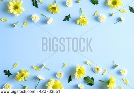 Frame Of Yellow Spring Flower Buds And Petals On Pastel Blue Background. Flat Lay Floral Composition