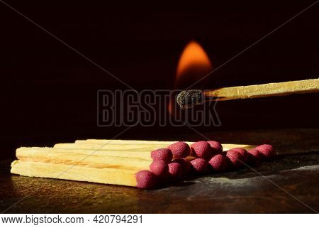 Starting A Fire. One Burning Match Ready To Burn Up Wooden Matches Lying In A Row. Isolated On A Bla