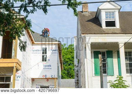 New Orleans, La - May 11: Worker Uses Air Hammer To Attach Shingles To Roof Of New House In Uptown N