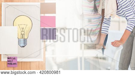 Composition of lightbulb image over two diverse businesswomen. global business, finance and networking concept digitally generated image.