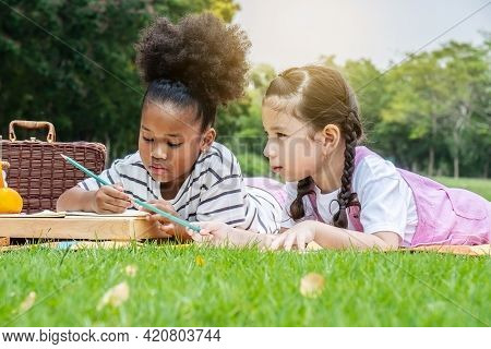 Two American African Little Girl Lying And Drawing With Colored Pencils At Summer Park, Feel Happine