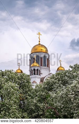 Blooming Apple Tree Against The Background Of The Orthodox Church And Cloudy Sky. Flowering Apple Tr