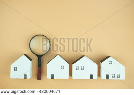 Magnifying Glass And Wooden Houses On A Yellow Background. Choice Of Location For The Construction.