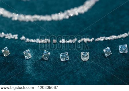 Lots Of Cut And Rough Diamonds Lie On The Green Velvet. Close-up Photo.