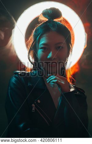 Color Night Portrait. Cyberpunk People. Futuristic Fashion. Blue Neon Light Smiling Asian Girl In Bl