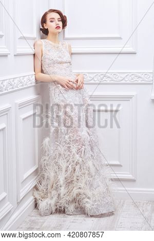 Full length portrait of a stunning young woman in a white wedding dress posing in a white room with classic interior. Fashion shot. Wedding dress.