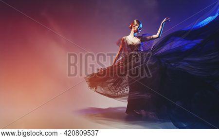 Art, ballet and fashion. Graceful female ballet dancer dancing in a fashionable evening dress. Ballet show. Full length studio portrait. Copy space.