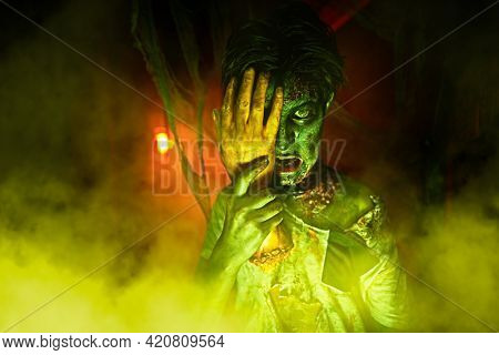 Halloween party. Angry and scary zombie boy teenager in red and green light.