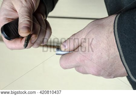 Man With Screwdriver In The Background Light Brown Cabinet Door. Close-up Of A Man's Hand Holding A