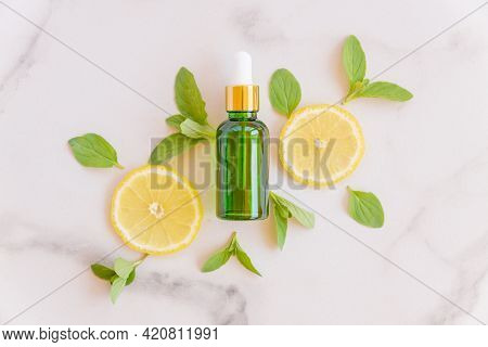 Vitamin C Serum In Cosmetic Bottle With Lemon Citrus Slices With Green Leaves On White Background. C