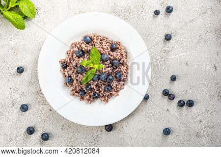 Delicious Risotto With Blueberries Served On Lihgt Grey Concrete Table, Flat Lay