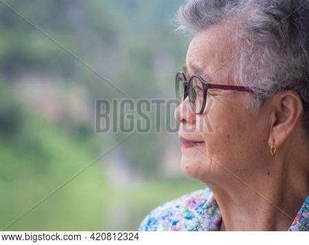 Side View Of An Elderly Asian Woman Smiling And Looking Away While Standing In A Garden. Concept Of