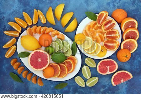 Citrus fruit to boost the immune system with oranges, lemons, limes and grapefruit on plates. High in antioxidants, anthocyanins, lycopene, fibre and vitamin c. Health care concept. On mottled blue.