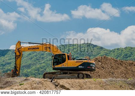 Daejeon, South Korea; May 2, 2021: Hyundai Backhoe At Rest On Top Of Dirt Hill At Construction Site.