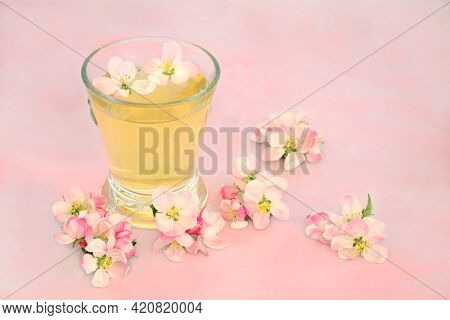 Natural remedy for skincare with apple blossom flowers with hot drink in a glass on pink marble. Can clear acne, provide a clear complexion and help with other skin problems. High in antioxidants.