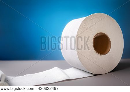 A Roll Of Toilet Paper On Blue Background Close-up. The Concept Of Panic Purchasing Of Essential Goo