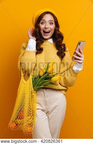 Smiling young woman with long red hair in sweater and beret standing holding tulips bouquet carrying bag with fruits over yellow wall background, holding mobile phone