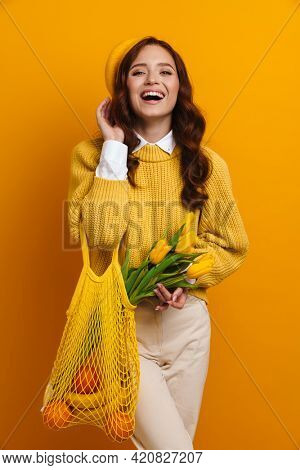 Smiling young woman with long red hair in sweater and beret standing holding tulips bouquet carrying bag with fruits over yellow wall background