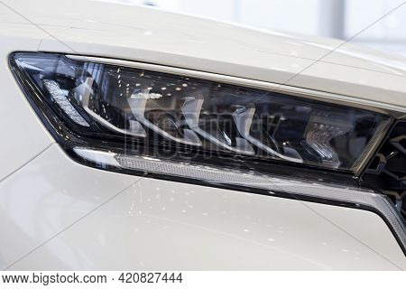New Modern Unknown Car With Elegant Head Lamps. Cropped Image. Close Up. Modern Transportation.