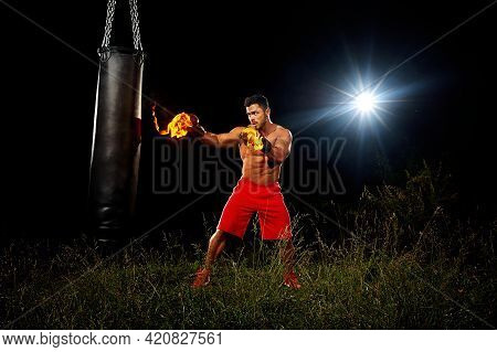 Sportsman Is Training On The Black Night Background, Muscular Body, Boxing Gloves In The Fire, The N