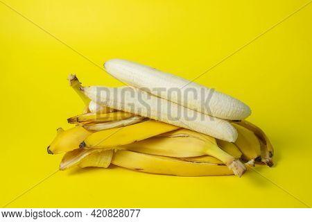 Bananas On A Yellow Background. Bright Fruits. Peeled Bananas On A Bunch Of Banana Peels.
