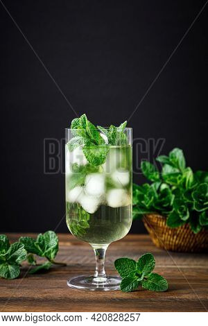 Iced Mint Tea, Refreshing Herbal Drink In A Glass With Ice And Fresh Leaves On Dark Background
