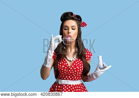 Portrait Of Young Happy Pinup Woman Wearing Red Polka Dot Dress, Blowing Soap Bubbles Over Blue Stud