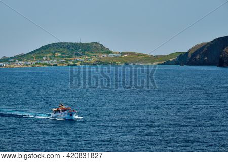 Greek fishing boat in blue waters of Aegean sea near Milos island, Greece