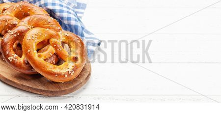 Fresh baked homemade pretzel with sea salt on wooden table. Classic beer snack. With copy space