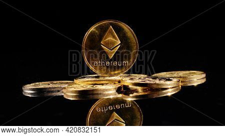 New Cryptocurrency Ethereum Eth 2.0 On A Top Of Bitcoin Coins Against Black Background. Closeup Gold