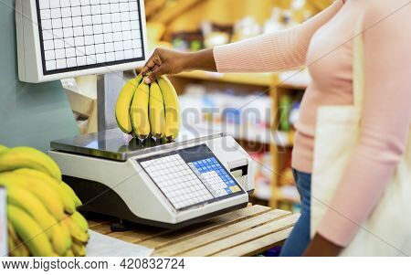Cropped View Of Young Black Woman Weighing Bananas On Scales At Supermarket, Closeup