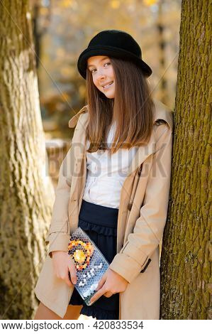 Love Wandering Alone. Soft Focus Shot Of A Happy Smiling Teen Holding A Book Posing Near A Tree