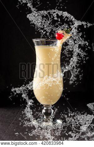 Pina Colada Cocktail Splashing In Glass On Black Background