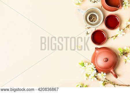 Asian Tea set on stone slate board, ceramic teapot, cups, dried tea and spring branches, tea ceremony , flat lay