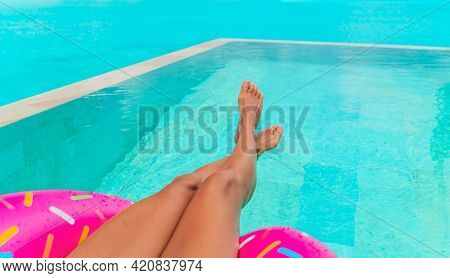 Travel vacation concept with bikini woman relaxing swimming in luxury infinity pool of Tahiti resort hotel lying in water floating on donut float in red bikini. Tanned slim body and hot legs.